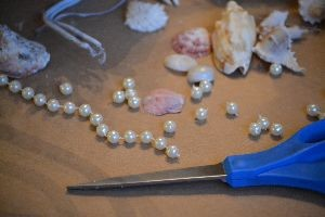 cutting up a long strand of pearl beads_small