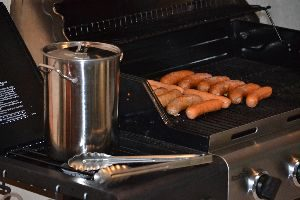 placing the brats on the grill to cook_small